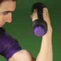 مرد ورزشکار در حال تمرین با دمبل تن زیب