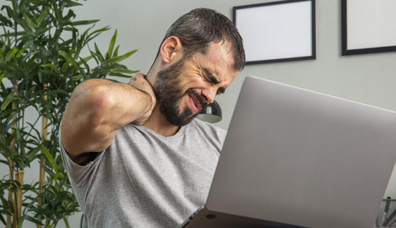 man-experiencing-neck-pain-while-working-from-home-laptop
