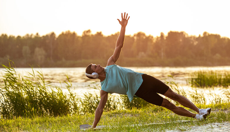 A young athletic man working out, training listening to music at riverside outdoors. Concept of healthy lifestyle, wellness, sport, activity, weight loss. Inspired of nature, summertime.