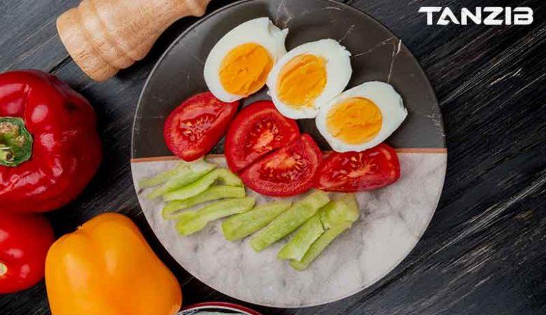 نمای بالای تخم مرغ آب پز در بشقاب با برش های گوجه فرنگی و فلفل دلمه ای رنگارنگ در زمینه چوبی
